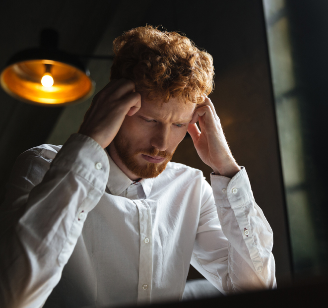 Picture of a frustrated man holding his head.