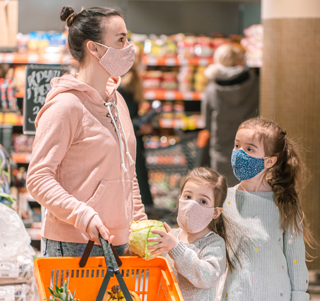 Picture of a mother grocery shopping with her two children.