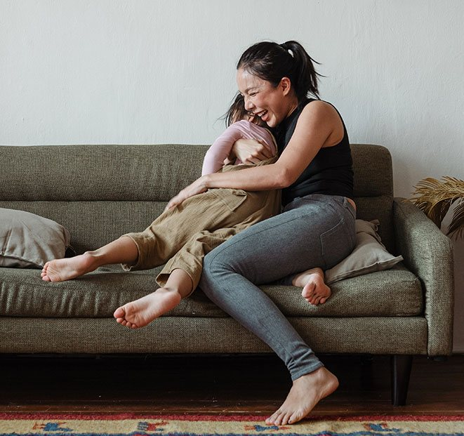 Mother playfully holding child while sitting on a couch
