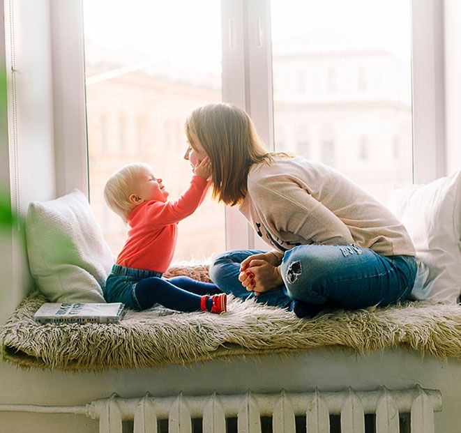 Mother and child sitting on window area while child is holiding moms face