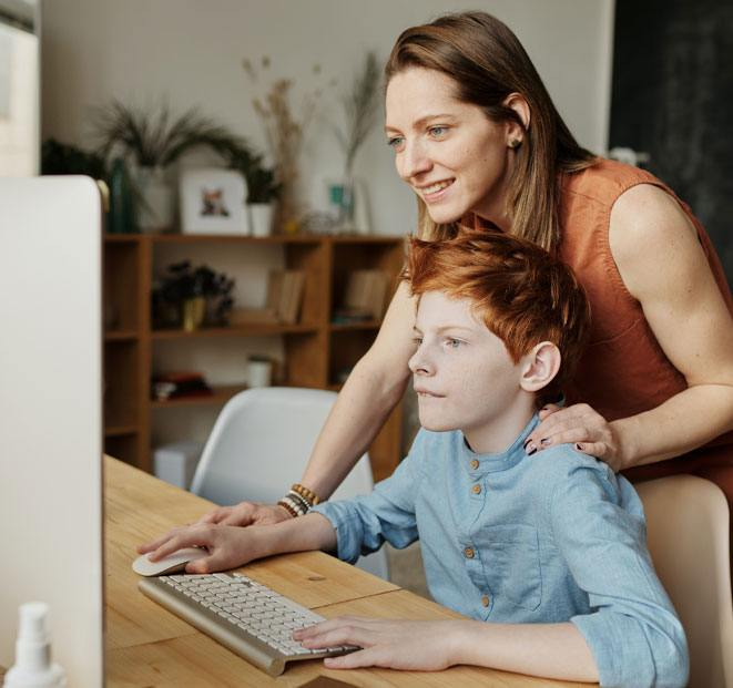 Mother and son looking at computer screen at a desk